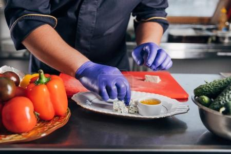 cropped shot of chef putting cheese pieces on plate