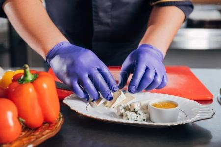 cropped shot of chef putting cheese slices on plate at restaurant