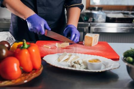cropped shot of chef slicing cheese at workplace in restaurant