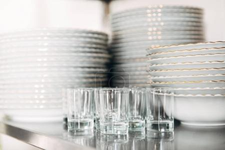 close-up shot of stacked clean tableware and glasses at restaurant