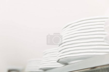 close-up shot of stacks of clean tableware at restaurant on shelf