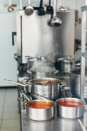 various soup cooking in sauce pans at restaurant kitchen
