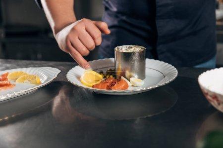 cropped shot of chef preparing salad at restaurant