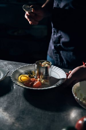 Photo for Cropped shot of chef preparing salad with metal forming tube at restaurant - Royalty Free Image