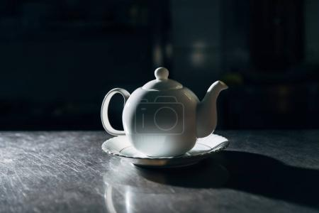 vintage teapot on plate on metal surface in dark room