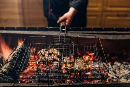cropped shot of chef cooking meat on flame in grill bar