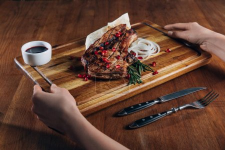 cropped shot of woman holding grilled steak served with sauce and pomegranate seeds on wooden board