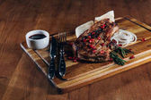 close-up shot of tasty grilled steak served with sauce and pomegranate seeds on wooden board