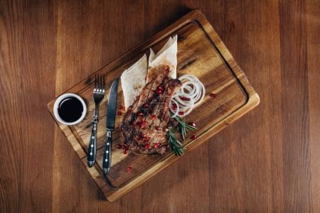 top view of grilled steak served with sauce and pomegranate seeds on wooden board