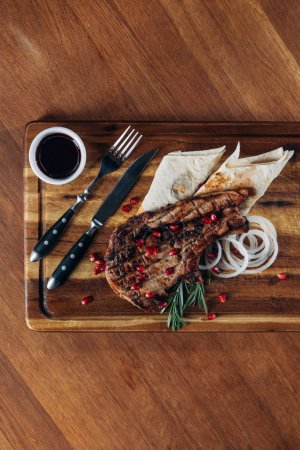 top view of delicious grilled steak served with sauce and pomegranate seeds on wooden board