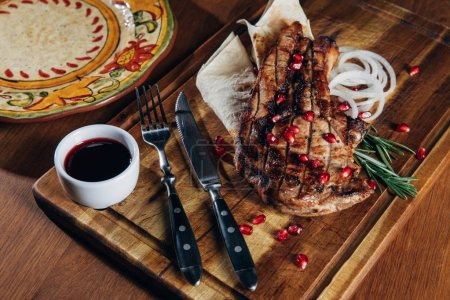 Photo pour Plan rapproché du steak grillé servi avec de la sauce et des graines de grenade sur une planche de bois - image libre de droit