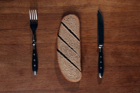 top view of sliced bread with cutlery on wooden board