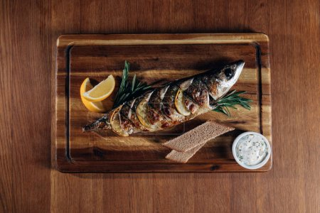 Photo for Top view of grilled fish with lemon and rye bread on wooden board - Royalty Free Image