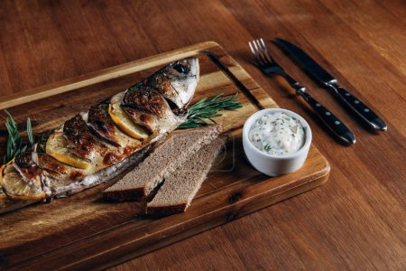 close-up shot of grilled fish with lemon and sauce on wooden board