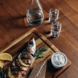 Постер, плакат: close up shot of grilled fish with lemon on wooden board with vodka in decanter and shots