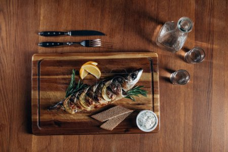 top view of grilled fish with lemon on wooden board with vodka in decanter and shots