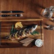 Постер, плакат: top view of grilled fish with lemon on wooden board with vodka in decanter and shots