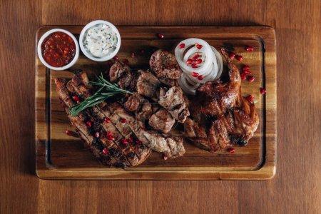 Photo pour Diverses grillades servies sur planche de bois avec sauces - image libre de droit