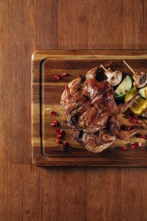 top view of delicious roasted quail with vegetables served on wooden board