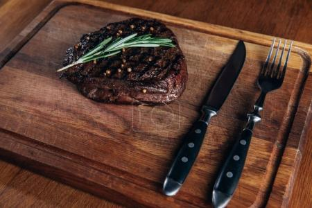Photo for Delicious grilled steak with cutlery on wooden board - Royalty Free Image