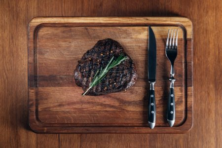 Photo for Top view of grilled steak with cutlery on wooden board - Royalty Free Image