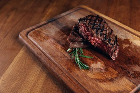 Photo for Medium rare grilled steak on wooden board - Royalty Free Image