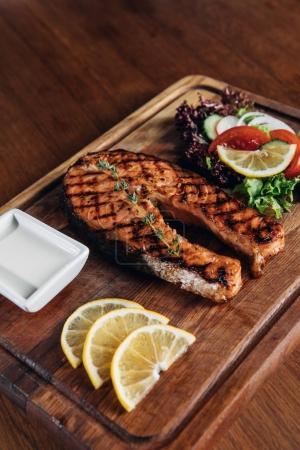 gros plan de Darne de saumon grillé servi sur planche de bois avec des tranches de citron et salade