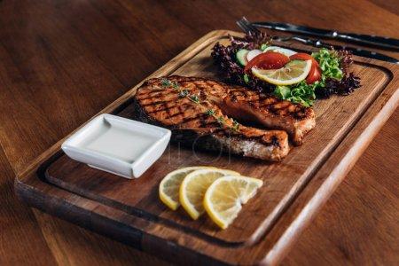Photo pour Plan rapproché de délicieux steak de saumon grillé servi sur une planche de bois avec citron et laitue - image libre de droit