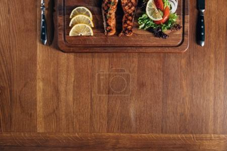 top view of tasty grilled salmon steak served on wooden board with lemon and lettuce