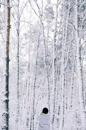 rear view of girl walking in snowy forest