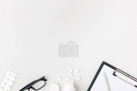 row of tablets, glasses and paper in folder isolated on white background