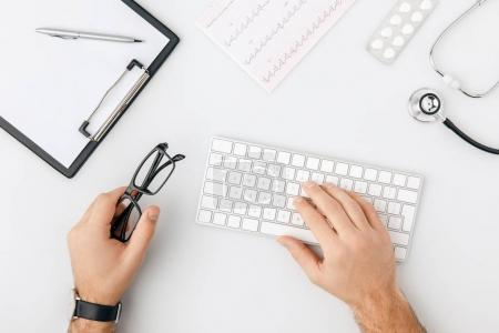 top view of hand with wristwatch on keyboard and with glasses in other hand isolated on white background