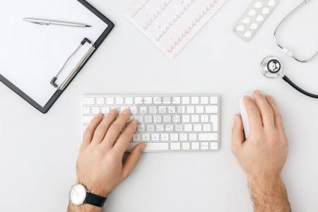 top view of hand with wristwatch on keyboard isolated on white background