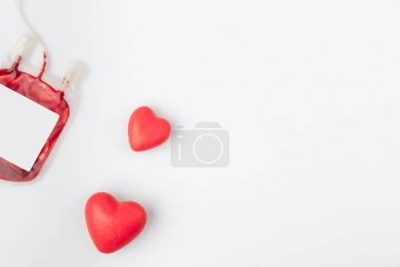 two red hearts near plastic package with blood for transfusion isolated on white background