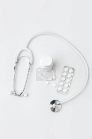 stethoscope,scattered pills and another tablets in package and in plastic can isolated on white background