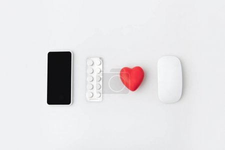 smartphone with blank screen, pills, hert and computer mouse isolated on white background in a row