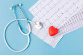 stethoscope, cardiogram and red heart isolated  on blue background