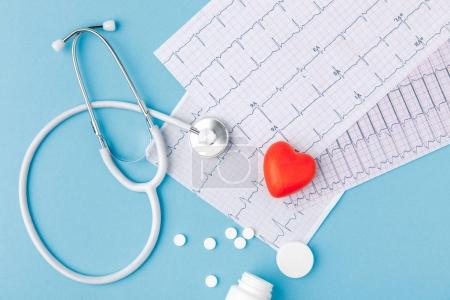 Photo for Stethoscope, paper with cardiogram, scattered pills and red heart isolated  on blue background - Royalty Free Image