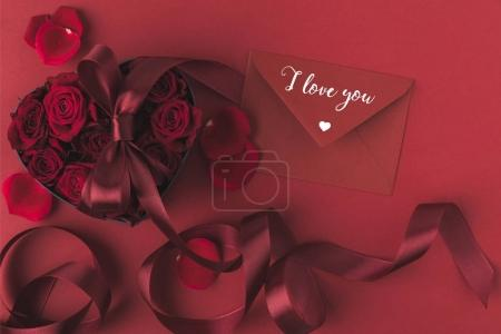 top view of roses in heart shaped gift box with ribbon and envelope isolated on red, st valentines day holiday concept