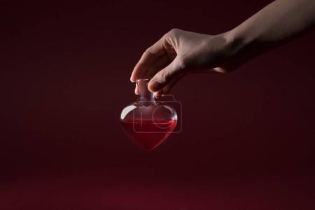 Photo pour Image recadrée de la femme tenant pot en verre en forme de coeur de potion d'amour isolé sur rouge - image libre de droit