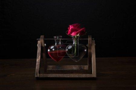 Photo pour Rose rouge en forme de coeur vase et vase avec élixir d'amour - image libre de droit