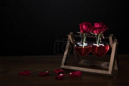 two red roses in heart shaped vases on wooden stand and petals on table