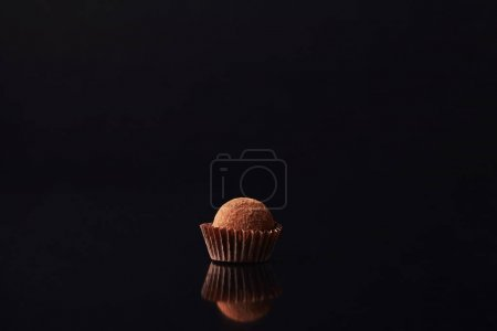 Photo for Close up view of sweet truffle candy on black - Royalty Free Image