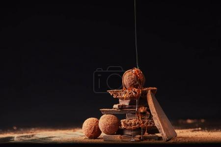 Photo for Close up view of process of pouring caramel onto truffles and chocolate bars with cocoa powder process on black - Royalty Free Image