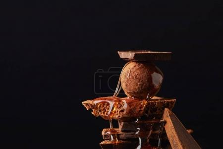 Photo for Close up view of arrangement of truffle with caramel and chocolate bars isolated on black - Royalty Free Image