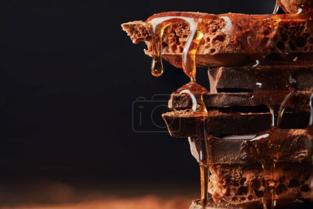 close up view of caramel on chocolate bars heap isolated on black