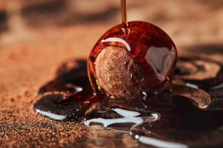 Photo for Close up view of pouring caramel onto truffle process - Royalty Free Image