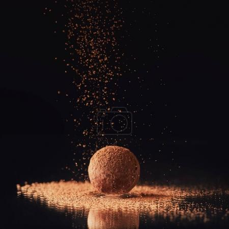 Photo for Close up view of sweet truffle candy with cocoa powder on black - Royalty Free Image