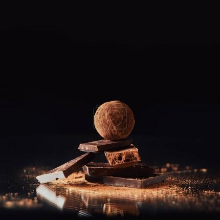 Photo for Close up view of truffle on chocolate bars with cocoa powder on black - Royalty Free Image
