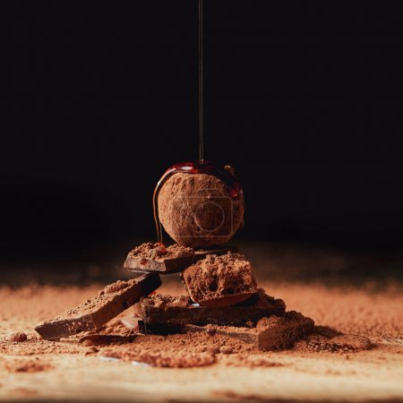 Photo for Close up view of pouring caramel onto heap made of truffle and chocolate bars on black - Royalty Free Image